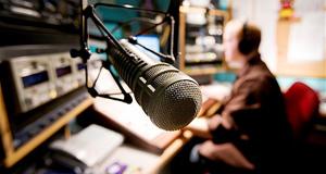 B31M3R A Radio DJ hosts a radio program from his studio.